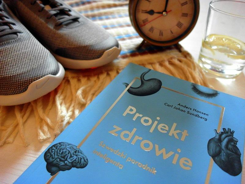 Zdjęcie przedstawia okładkę książki Projekt zdrowie. Na drugim planie widać sportowe buty, budzik i wodę z cytryną.